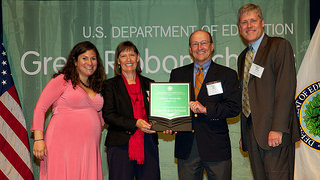 Photo of Dr. Nanette Chadwick and Mike Kensler accepting the US Department of Education Green Ribbon Schools Award from Department of Education officials.