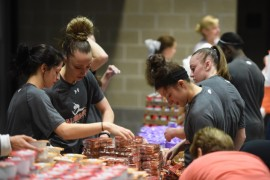 Photo of Volunteers in athletics filling backpacks for the End Child Hunger in Alabama campaign.
