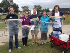 Photo of Office of Sustainability interns and staff handing out recycling bags and Green Game buttons to tailgaters. From left to right: Rebecca Oliver, Amy Strickland, Taylor Craft, Jennifer Morse, and Kyle Kimel.