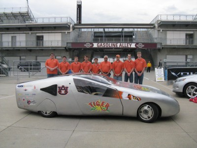 Photo of Dr. Sushil Bhavnani (fourth from right) with the TIGER car student team at the Indianapolis Motor Speedway.