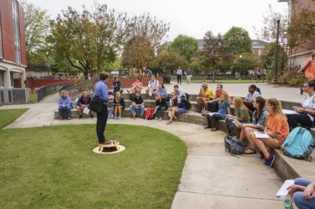 Photo of students listening to a lecturer in an outdoor setting.
