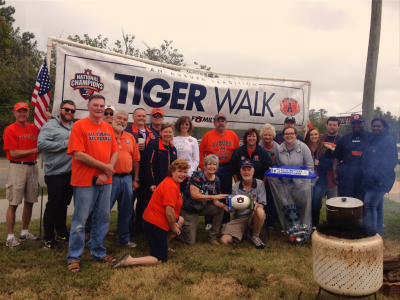 Tailgaters pose with the Gus Malzahn signed football they won by getting caught recycling at their tailgate.
