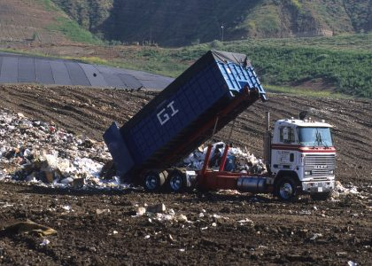 Photo of dump truck unloading at a landfill.
