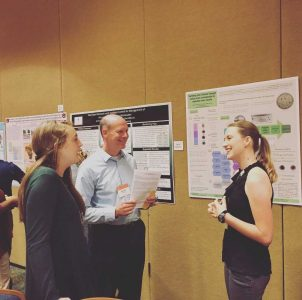 Attendees of conference discuss poster.