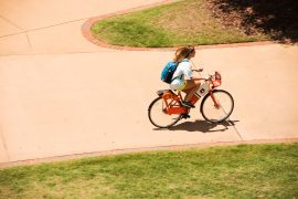 Student riding a bike share bike on campus