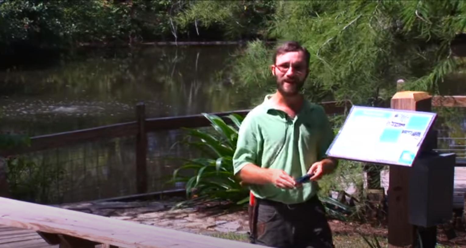 Photo of Patrick Thompson standing beside an interpretative sign at the Arboretum.