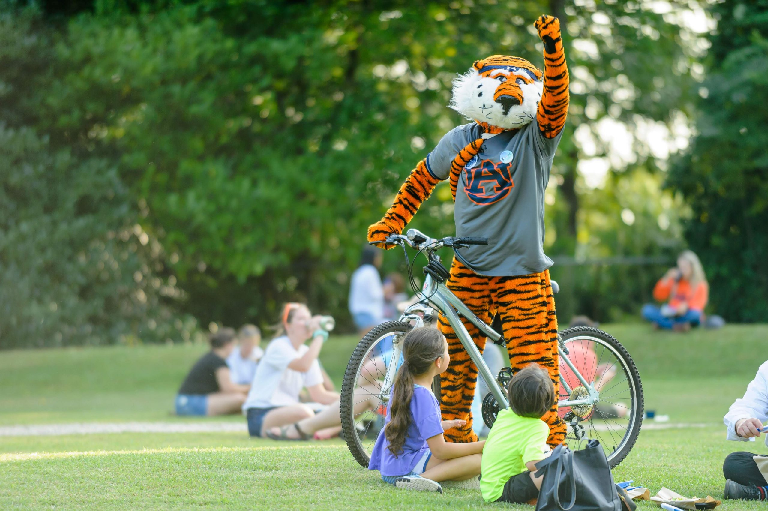 Photo of Aubie on a bicycle with his fist raised.