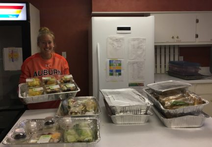 Kenzley Defler with packaged food from a Campus Kitchens Project packaging shift.