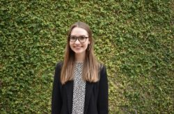 Campus Changemaker Lauren Lavender posed in front of the Student Center green wall.