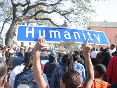 """A person holding up a street sign titled """"humanity"""" while marching"""