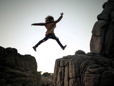 woman leaping over space between rocks