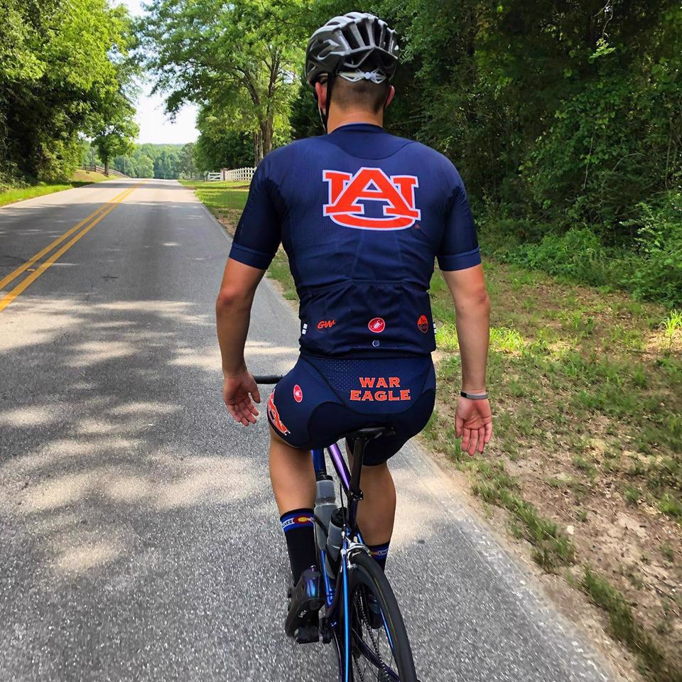 Photo of person riding a bicycle with an Auburn biking uniform on.
